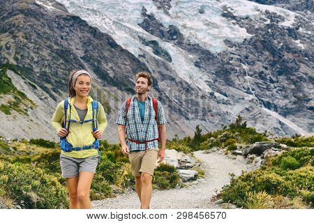 Hiking travel hikers people tramping in New Zealand mountains nature trail. Backpackers couple on Mount Cook / Aoraki Hooker valley track backpacking walking. Snow capped glacier landscape. poster