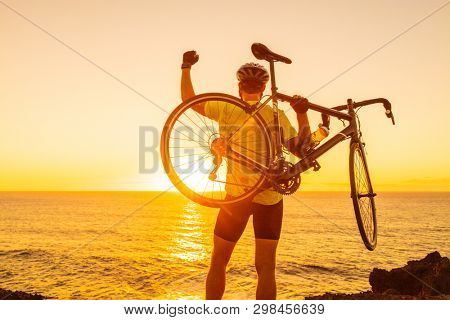 Success, achievement and winning concept with cyclist man road biking. Happy male professional athlete cycling raising arms lifting bike by sea during sunset cheering and celebrating at summit top.
