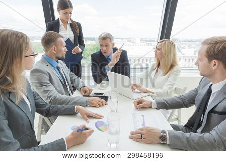 Mixed group of white collar workers at business meeting discuss documents