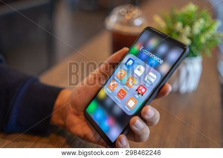 Chiang Mai, Thailand - Mar. 24,2019: Man Holding Xiaomi Mi Mix 3 With Icons Of E-commerce And Online