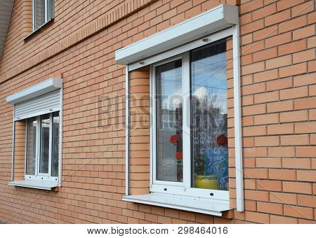 Rolling Shutters House Windows Protection. Brick House With Metal Roller Shutters On The Windows