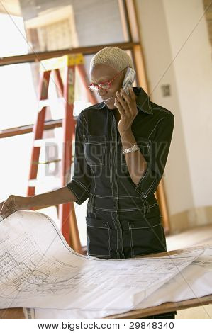 Young businesswoman examining blueprints