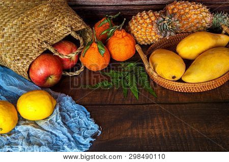 Photo Of Basket Full With Delicious Tropical Fruits In Front Of A Rural Background.