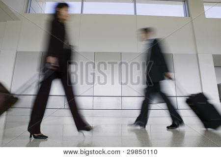 Blurred motion businesspeople with luggage