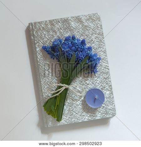 A Notebook On A White Background, Silver Cover, A Bouquet Of Blue Spring Flowers, A Blue Candle