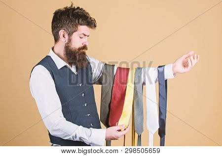 Tie The Perfect For Daily Wear. Bearded Man Choosing Neck Tie. Brutal Hipster Holding Colorful Tie C