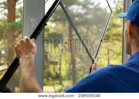 Man Installing Mosquito Net Wire Mesh On House Window