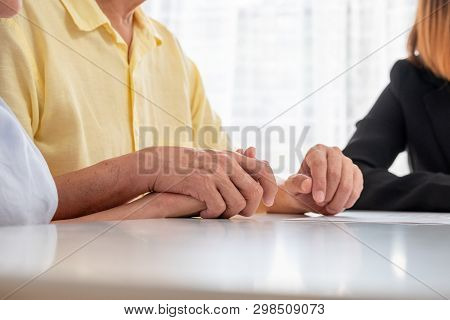 Asian Senior Couple Holding Hand With Careless And Talk With Financial Advisor About Tax And Retirem