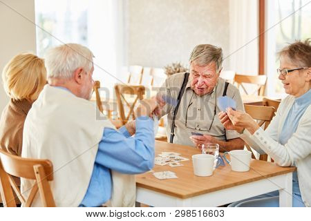 Senior friends play cards in a tournament at the retirement home or at home