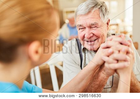 Nursing lady consoles senior man on a home visit and gives him hope