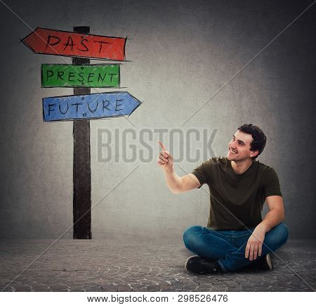Young Man Sitting On The Floor Pointing Forefinger At Signpost Arrows Shows Past, Present And Future