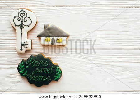 Moving in new house, Welcome home set. Key, house, welcome sign cookies on white wood, flat lay with space for text. Dream home concept. Home Sweet Home. poster