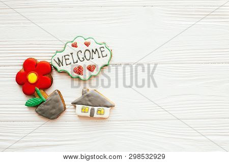 Moving in new house, Welcome home set. House, plant,heart, welcome sign cookies on white wood, flat lay with space for text. Dream home concept. Home Sweet Home. poster
