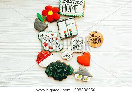 Welcome home set. Delicious key, house, plant,window,heart and welcome sign cookies on white wood, flat lay with space for text. Dream home concept. Home Sweet Home. Moving in new house poster