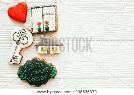 Moving in new house, Welcome home set. Key, house, plant,heart, welcome sign cookies on white wood, flat lay with space for text. Dream home concept. Home Sweet Home. poster