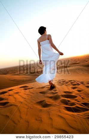 young woman in sandy desert at sunset