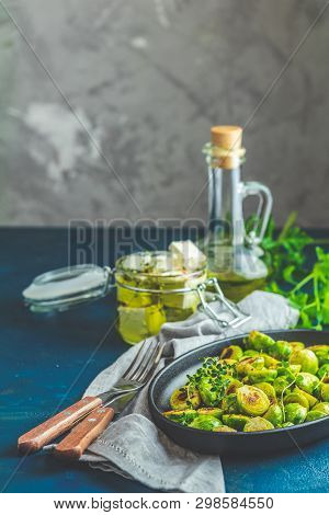 Black Plate With Delicious Roasted Brussels Sprouts In Served On Black Plate, Dark Blue Concrete Tab