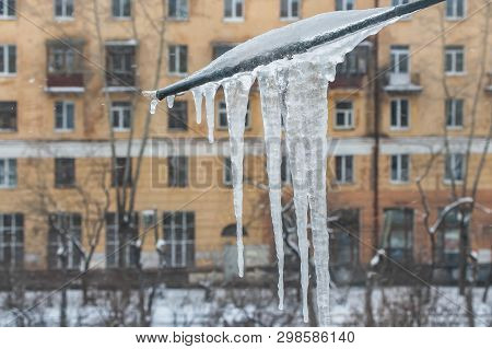 View Through A Window With A Group Of Sharp Bright White Transparent Icicles Outside On Tv Antena To