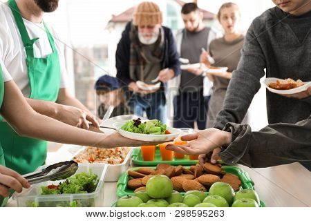 Volunteers Giving Food To Poor People Indoors