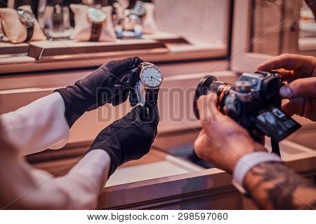 Tattoed Photographer Is Taking Photo Of Expensive Watch In Posh Shop, While Shop Assistant Is Holdin