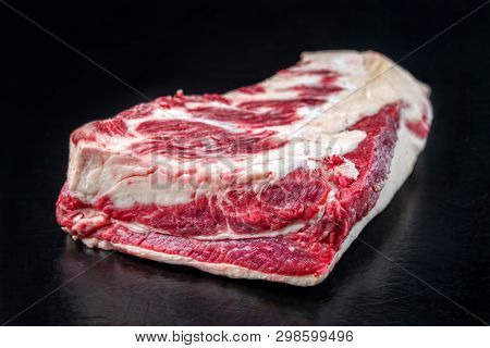 Raw dry aged wagyu beef brisket piece as closeup on black background with copy space