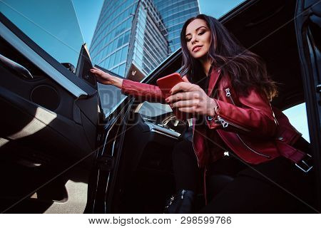Young Attractive Women Is Posing In Her New Car While Chatting On Mobile Phone. She Is Wearing Red L