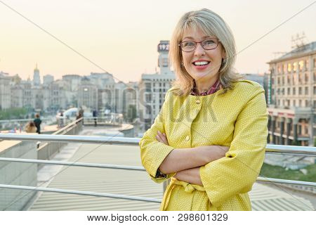 Outdoor Portrait Of Mature Smiling Woman With Glasses, Yellow Raincoat. Woman 40, 45 Years Old, Spri