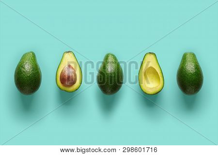 Row Of Fresh Wholes And Halves Of Organic Avocado With Kernels In Center On Blue Backgrond. Top View