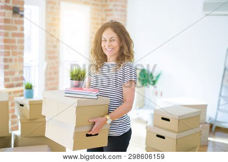 Middle age senior woman smiling happy holding cardboard boxes, packing moving to a new house