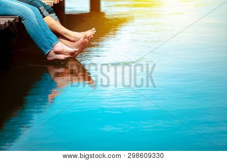 Romantic Couple Man And Woman Are Sitting On A Dock With Barefoot Feet Dangling In Pond Water. Sunny