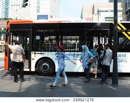 Jakarta, Indonesia - April 17, 2019: Some Passengers Getting Off The Metrotrans Bus At The Bus Stop