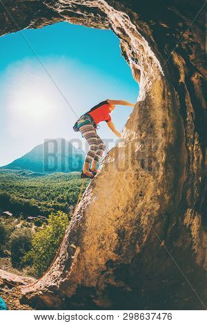 A Woman Trains On A Natural Rocks. The Girl Overcomes The Difficult Climbing Route On The Turkish Ro