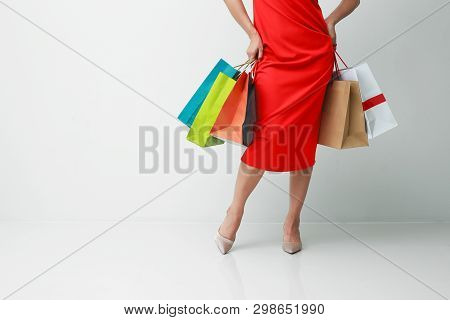 Happy Shopping. Woman In Red Pants Holding Multicolored Shopping Bags