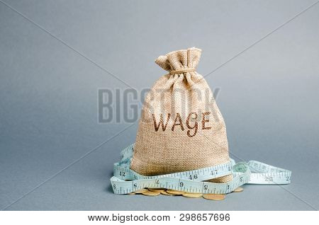 Money Bag With The Word Wage And Tape Measure. Wage Cuts. The Concept Of Limited Profit. Lack Of Mon