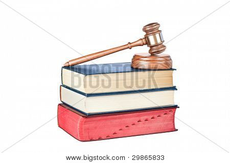 A gavel and sound block on thick legal reference books isolated on white.