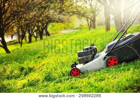 Gardening Care, Mowing Trim Green Grass On Lawn Hill With Lawnmower.