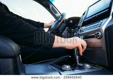 Gear Shift In The Car, The Driver's Hand On Shifting The Gear Stick