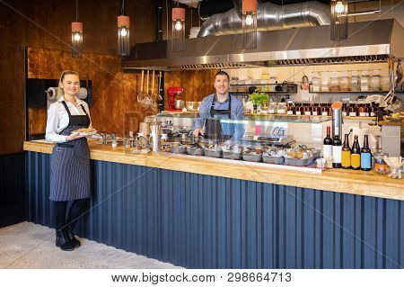 Counter Service At Modern Bistro With Smiling Waiters Serving Food - Happy Business Owners In Small