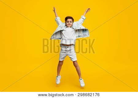 Full length stylish youngster with raised hands looking at camera and leaping up against yellow background poster