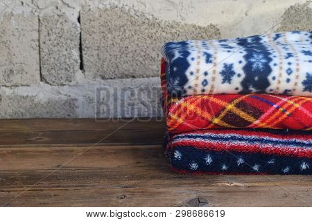Stack Of Warm Woolen Blankets On Wooden Background. Home Cosiness. Colorful Plaids.