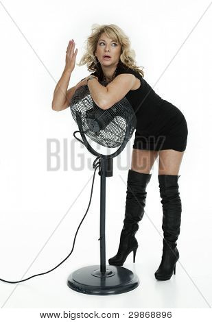 Menopausal woman standing, leaning over fan to cool off, shot on white background.