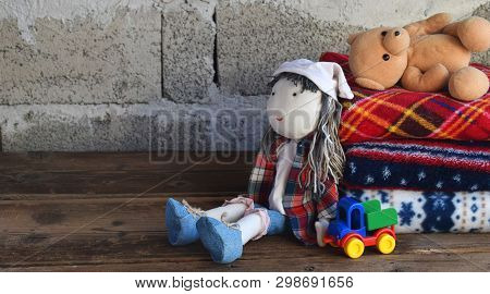Stack Of Warm Woolen Blankets And Doll On Wooden Background. Childrens Textile Toys. Home Cosiness.