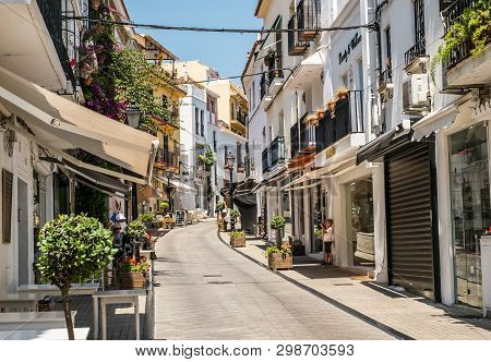 Marbella, Spain - June 27th, 2018. The Little Photographer On Old  Town Street In Marbella, Costa De