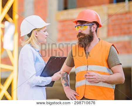 Woman Engineer And Bearded Brutal Builder Discuss Construction Progress. Construction Project Manage