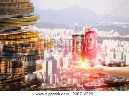 Us Dollar And China Yuan Banknote On Hand With City Landscape. It Is Sign For Battle Tariff Trade Wa