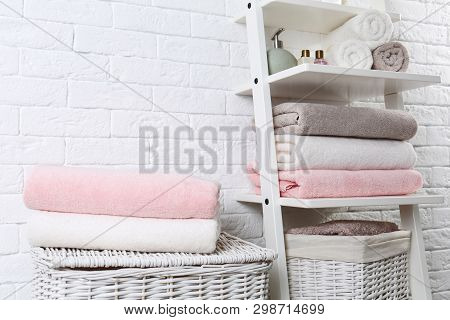 Shelving unit and baskets with clean towels and toiletries near brick wall poster