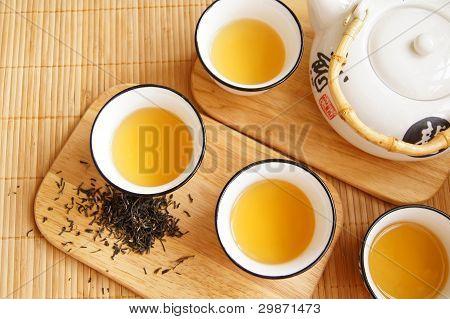 Primer plano de conjunto del té de China en la estera de bambú