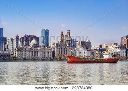 1 December 2018: Shanghai, China - Cargo Ship On The Huangpu River Passing The Bund, The Historic Bu