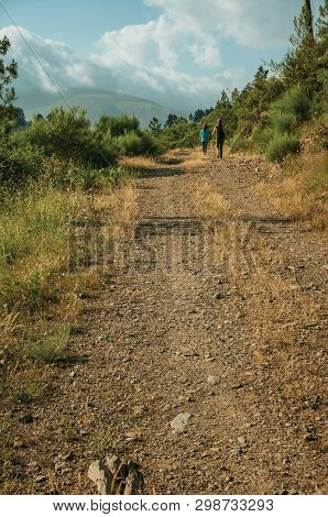 People Hiking On Dirt Road Through Hilly Landscape