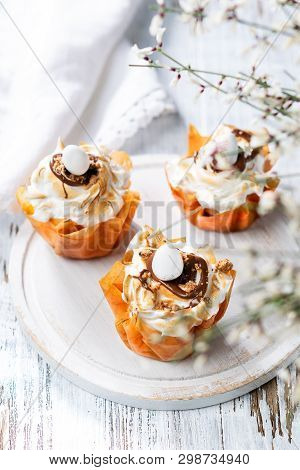 Fancy Phyllo Dough Cups With Meringue And Melted Chocolate Close Up On A Plate. White Rustic Backgro